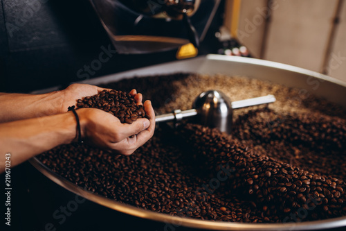 Freshly roasted coffee beans pouring from a large coffee roaster into the cooling cylinder. - 219670243