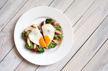 The fried egg in the form of heart with vegetables and bread on a white plate