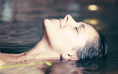 Woman having a bath in a whirlpool bath in a spa © Minerva Studio