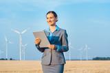 Investorin in Windkraftanlage betrachtet ihre Geldanlage  - 219692268
