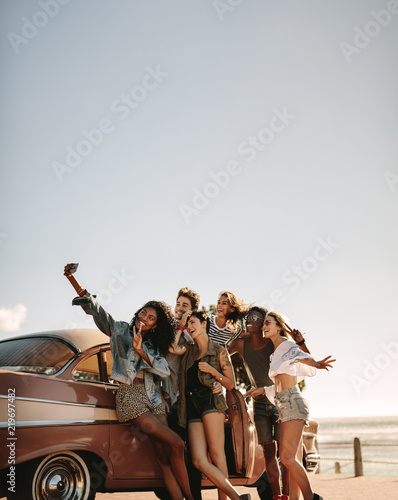 Multi ethnic friends taking a selfie near the car - 219697482