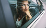 Female business executive travelling by a cab - 219698636