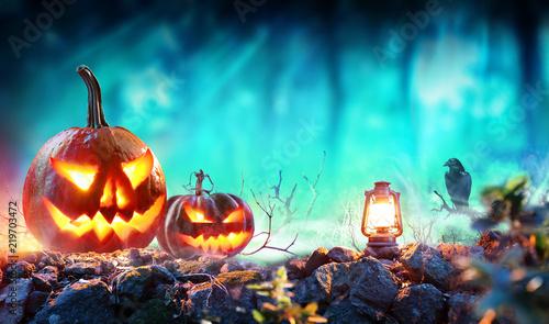 Leinwanddruck Bild Halloween Pumpkins In Spooky Forest With Lantern And Crow