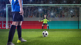 kid football player prepairing to take a shot on a football field - 219707494