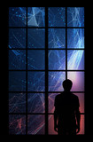 Back view of man standing in front of the big window and looking at futuristic cyberspace sphere. - 219708074