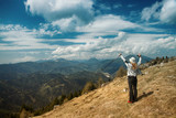Happy woman on top of the hill with sunny and cloudy sky background. - 219708473