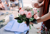 Woman is crafting rose flower bouquet on the wooden table - 219711474