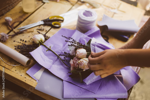 Leinwanddruck Bild Woman is crafting rose flower bouquet on the wooden table