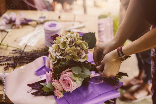 Woman is crafting rose flower bouquet on the wooden table - 219711479