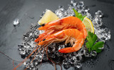Shrimps. Fresh prawns on a black background. Seafood on crashed ice with herbs. Healthy food, cooking - 219715856