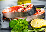 Salmon. Raw trout fish steak with herbs and lemon on black slate background. Cooking, seafood. Healthy eating concept - 219716071