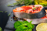Salmon. Raw trout fish steak with herbs and lemon on black slate background. Cooking, seafood. Healthy eating concept - 219716415
