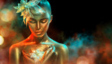 Fashion model woman in colorful bright golden sparkles and neon lights posing with fantasy flower. Portrait of beautiful girl with glowing makeup - 219716476