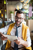 Portrait of  handsome bearded businessman wearing glasses sitting at bar counter using digital tablet  and smiling cheerfully - 219722040