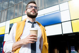 Low angle portrait of contemporary entrepreneur drinking coffee outdoors in sunlight, copy space - 219722278