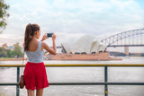 Sydney travel tourist woman taking phone picture of Opera house on Australia vacation. Asian girl using cellphone for photos during holiday. - 219725650