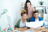 Multi-ethnic group of contemporary young business people discussing documents while working at desk in modern office, all dressed in business casual - 219733000