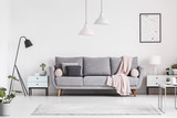 Grey couch with blanket between cabinets in living room interior with poster and lamps. Real photo - 219740841