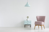 Pink chair next to cabinet with plant in apartment interior with lamp and copy space. Real photo with a place for your poster - 219740856
