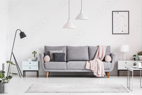 Grey couch with blanket between cabinets in living room interior with poster and lamps. Real photo © Photographee.eu