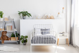 Gray bedding on a single bed with metal frame and a scandinavian style nightstand in a beautiful, bright kid bedroom interior with natural light