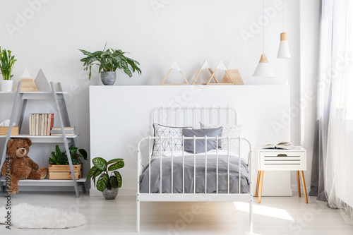 Leinwanddruck Bild Gray bedding on a single bed with metal frame and a scandinavian style nightstand in a beautiful, bright kid bedroom interior with natural light