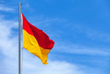 Red and yellow flag on a beach over blue sky - 219745683
