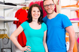 Happy couple shopping clothes in fashion store - 219749062
