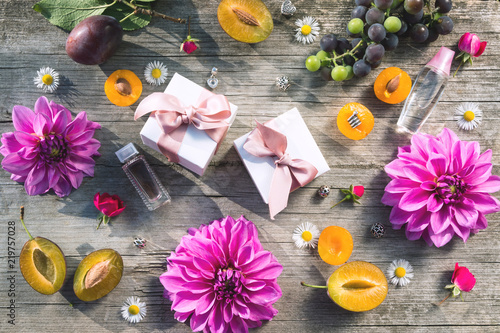 Autumn background of flowers dahlias and fruits. Boxes with jewelry of a famous brand popular all over the world. Silver and gold bracelets with charms. Free space for text. Flat lay.