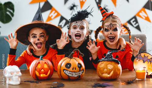 Leinwandbild Motiv happy Halloween! a group of children in suits and with pumpkins in home
