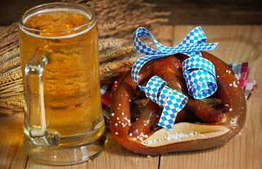 Pretzel with glass of beer on wood table,Oktober background.