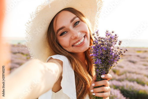 Lovely young girl in straw hat holding lavender bouquet - 219760295
