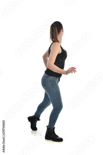 926e3311f61 full length portrait of brunette girl wearing black single and jeans.  standing pose with back