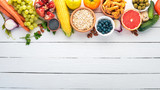 Healthy food on a white wooden table. Fresh vegetables, fruits, nuts, berries, mushrooms. Top view. Free space for text. - 219767400