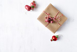 Rustic Christmas gift box with Christmas decorations on white wooden background. Flatlay. Copy space - 219767432