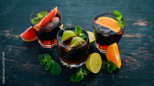 Cocktails with citrus fruit and mint. Lemon, grapefruit, lime, orange. On a wooden background. Top view. - 219767449