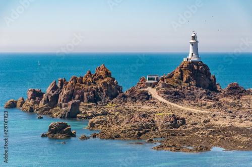 Leinwanddruck Bild La Corbiere lighthouse on the island of Jersey at low tide