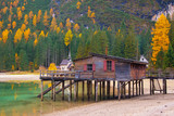Beautiful autumn alpine landscape, spectacular old wooden dock house with pier on Braies lake, Dolomites, Italy - 219769453