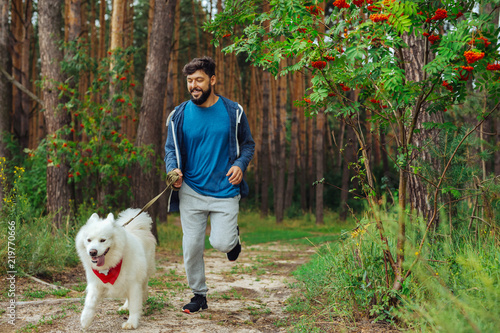 Running in forest. Bearded handsome man wearing sport suit feeling amazing while running with dog in the forest