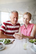 Mature woman with smartphone and her husband communicating through video-chat while sitting by lunch