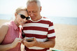 Restful senior couple watching curious video in smartphone or communicating through messages or video-chat