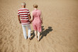 Affectionate senior couple in casualwear walking down sandy beach on hot summer day