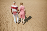 Affectionate senior couple in casualwear walking down sandy beach on hot summer day - 219772451