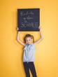 Leinwanddruck Bild - schulkind hält schild oder tafel mit der aufschrift endlich wieder schule vor hintergrund zum schulbeginn