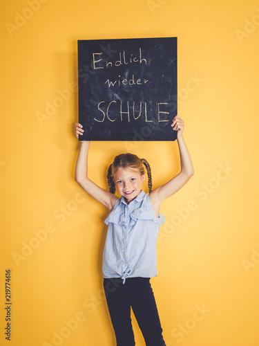 Leinwanddruck Bild schulkind hält schild oder tafel mit der aufschrift endlich wieder schule vor hintergrund zum schulbeginn