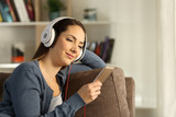 Relaxed woman listening to music on a couch