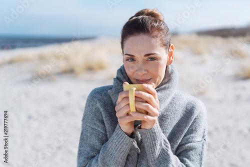 Leinwandbild Motiv entspannte frau mit einer tasse heißen tee am meer