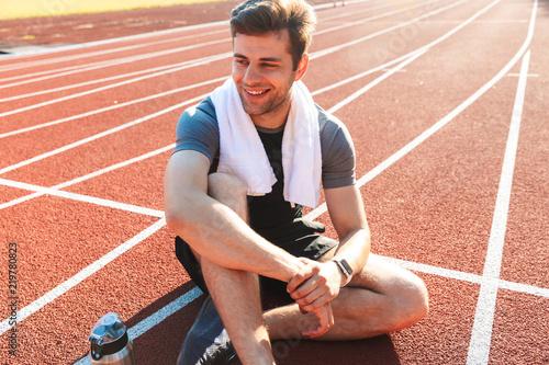 Leinwanddruck Bild Smiling sportsman finished running at the stadium