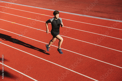 Wall mural Focused young sportsman running