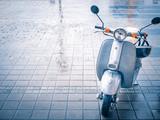 cute small vespa motobike scooter at paving stone
